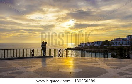 Mature female photographer taking pictures at Balcon de Europa and looking the magnificent sunrise Nerja Spain