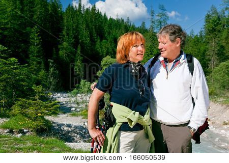 a senior couple is hiking in the mountains