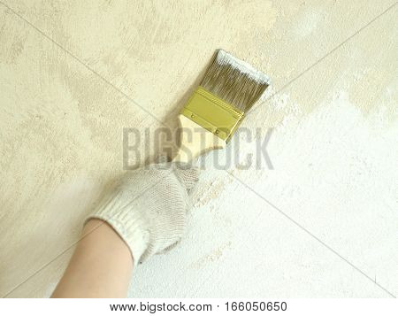 Woman's hand in white fabric protective glove holds brush and paint wall repair vertical photo