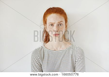 Portrait Of Young Annoyed Female With Freckles And Pursed Lips Having Disappointed Unhappy Look, Fro