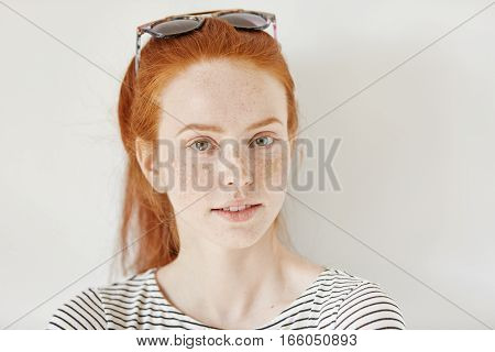 Indoor Shot Of Attractive Redhead Woman Model With Freckles Wearing Trendy Sunglasses On Her Head An