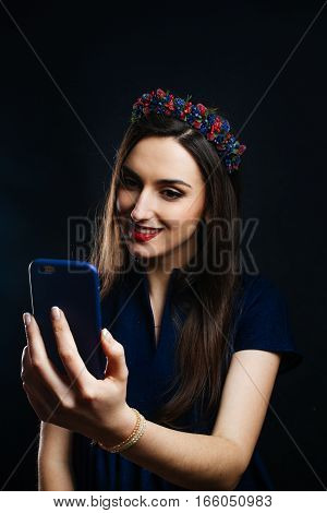 Girl in the wreath is taking selfie. She has a nice day she is smiing on the phone