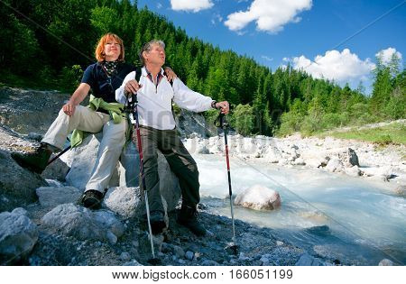 a senior couple is hiking in berchtesgaden bavaria, germany , sitting next to a small river and enjoying the view