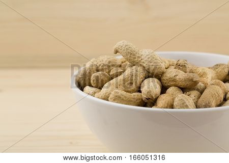 Roasted peanuts in bowl over wooden background