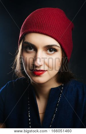 Portrait of pretty girl in red hat. She dreams and smiles. Studio shot of a magnificent young woman in a fitting dress and elegant classic hat. Beauty fashion concept.