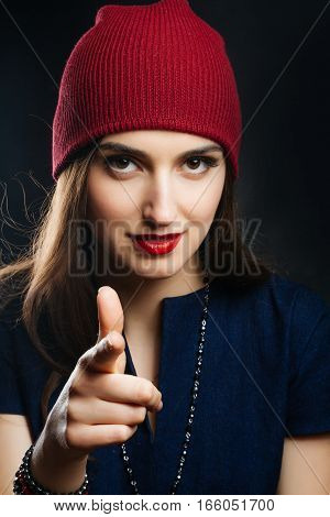 Portrait of pretty girl in red hat. She points a finger at you. Studio shot of a magnificent young woman in a fitting dress and elegant classic hat. Beauty fashion concept.