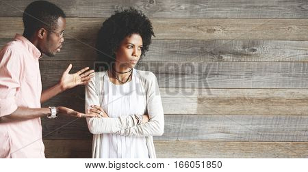 Relationship problems. Frustrated young African couple having argument and quarrelling with each other: man in glasses complaining to his girlfriend who is not looking at him keeping her arms crossed