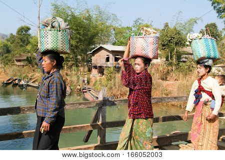 Indein Myanmar - 15 January 2010: Woman carrying merchandise for the weekly market at Indein on Inle Lake in Myanmar