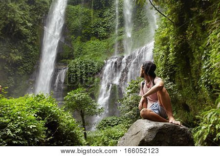 Tourism, Travel And Adventure. Stylish Young Hipster Sitting On Stone With Bare Feet And Turning His