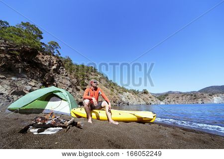Camping with kayaks on the beach in the summer on a sunny day.