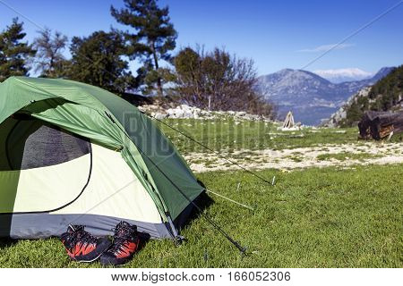 Camping with a tent in the mountains on a sunny day.