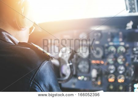 People, Lifestyle And Occupation Concept. Rear View Of Commercial Pilot Wearing Headset And Uniform