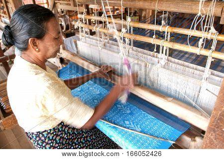 Lake Inle Myanmar - 15 January 2010: Woman weaving a carpet with a loom at lake Inle on Myanmar