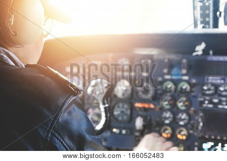 Caucasian Captain Piloting Airplane. Backview Of Professional Aviator In Sunglasses And Outfit Flyin
