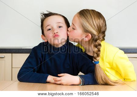 Pretty young girl gives her little brother a kiss at home in the kitchen