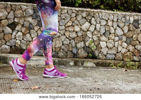 Outdoor Portrait Of Female Runner With Fit Athletic Legs Wearing Purple Sneakers Walking Along Concr
