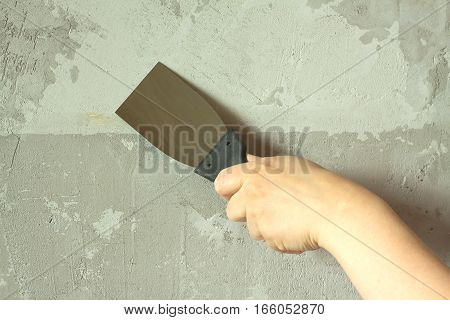 Woman's hand with a spatula wall plasters in room during repair horizontal photo