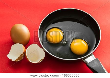 raw egg in pan on red background