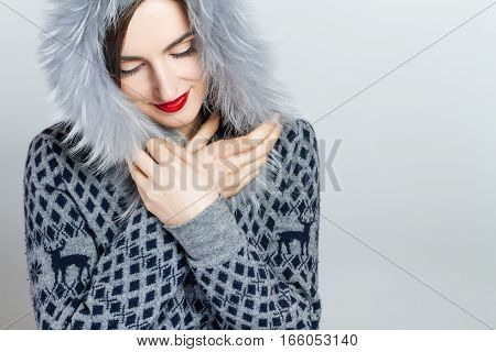 Winter beauty fashion. Beautiful face girl with trendy fur hat gesturing. Emotions. Professional makeup and manicure. Portrait on grey background. Celebrating the New Year and Christmas