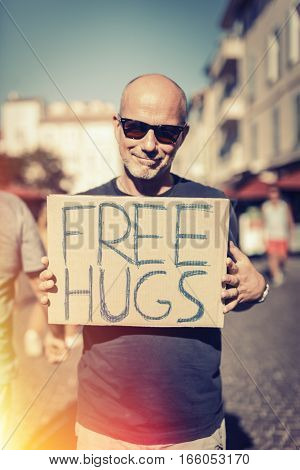 Man holding FREE HUGS sign in european city