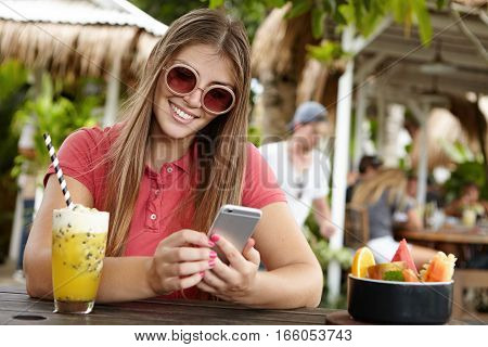 Modern Technology, Leisure And People Concept. Cute Woman In Shades Texting Messages To Her Friend U