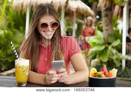 Stylish Girl With Long Hair Messaging Friends Via Social Networks On Her Cell Phone, Looking At Scre