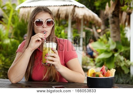 Happy Young Woman On Holidays Sipping Fresh Drink. Attractive Caucasian Female In Trendy Round Shade