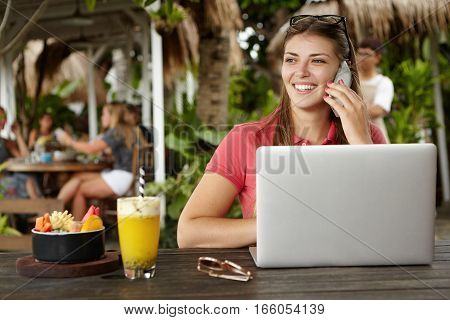 Outdoor Shot Of Attractive Cheerful Businesswoman With Glasses On Her Head Sitting At Sidewalk Resta