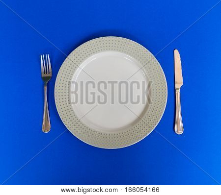 Dish spoon and fork on blue background