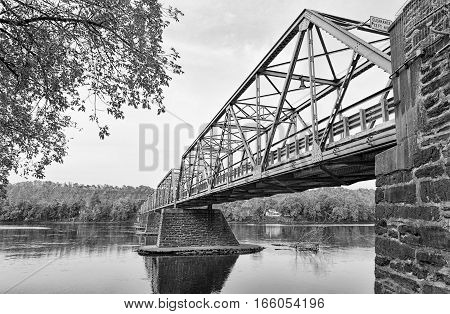 The Uhlerstown-Frenchtown Bridge from Frenchtown New Jersey to Uherlstown Pennsylvania. The bridge crosses the Delaware River. The photo is in black and white.