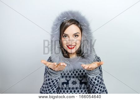 Winter beauty fashion. Beautiful face girl with trendy fur hat gesturing.