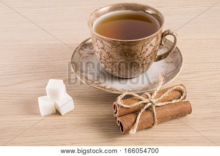 Brown tea cup and saucer, a bundle of cinnamon and sugar on light wooden background.