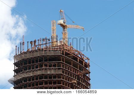Yellow hoisting tower crane in construction process on top of construction modern building over sky with clouds
