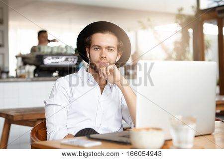 Cheerful Young Freelancer Having Break During Remote Work At Coffee Shop, Sitting At Table With Elec
