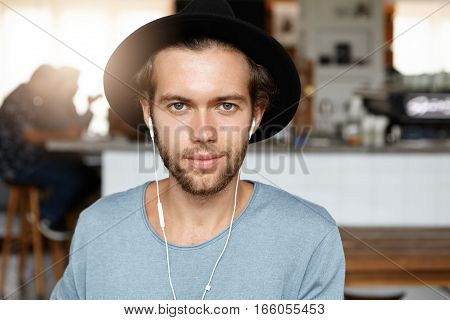 Fashionable Young Bearded Male Looking At Camera With Joyful Smile While Having Video Chat To His Fr