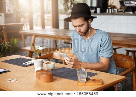 Fashionable Young Bearded Man In Black Hat Checking His Newsfeed On Social Media And Listening To So