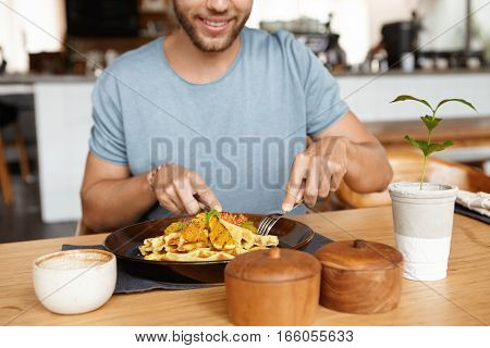 Cropped Portrait Of Happy Young Bearded Male In T-shirt Smiling Cheerfully While Enjoying Tasty Meal
