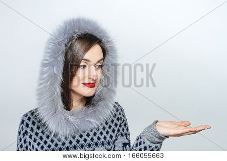 Winter beauty fashion. Beautiful face girl with trendy fur hat gesturing. Emotions.