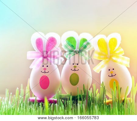 Colored easter eggs bunny on grass over light background