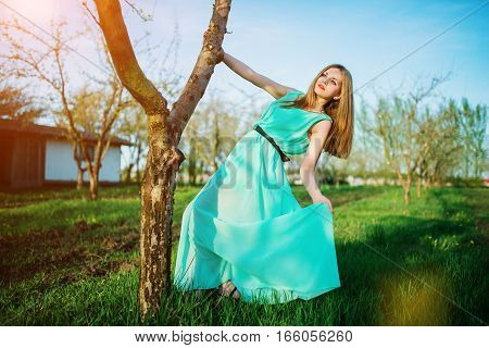 Woman In A Beautiful Long Turqoise Dress Posing On A Meadow In The Fruit Garden.