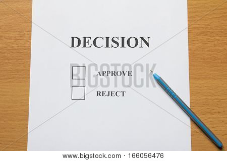 Decision paper (approve reject) with pen on wooden background
