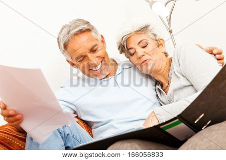 Studio shot of senior couple doing paperwork