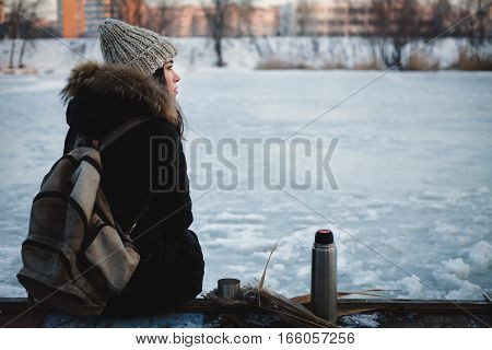 Girl drinking hot tea outdoors in winter
