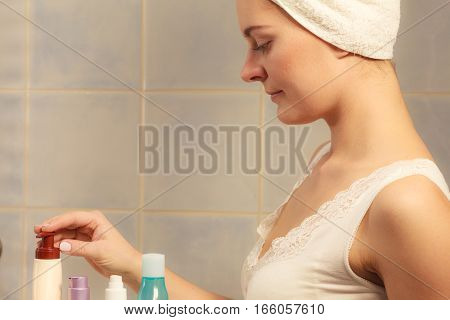 Woman In Bathroom With Bottles Cosmetics