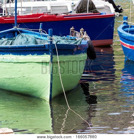 Small traditional fishing boat made of wood coloured painted Sicily