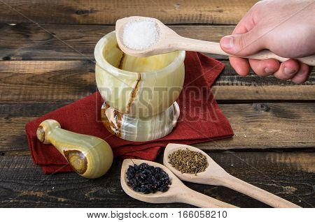 man throws salt in a mortar on a wooden background