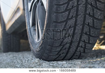 Close up of car's winter tyre tread on the gravel road