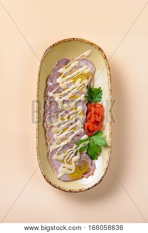 Beef tongue slices decorated with vegetables and sause