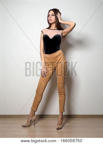 Young woman in black blouse and beige pants posing over white wall