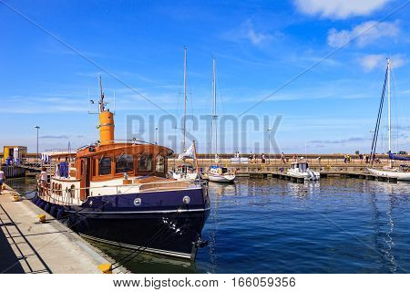 HEL, POLAND - AUGUST 10 2015: People walking through in the port on the waterfront with many boat and sailboat in Hel. Hel is one of most famous cruise travel destinations in Poland.